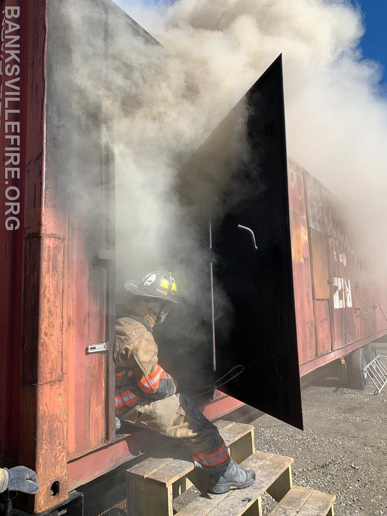 An instructor from Flashfire industries controlling the ventilation conditions with the side door of the trailer.